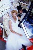 Portrait of a newlywed couple sitting in a convertible car