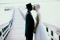 Side profile of a newlywed couple kissing on a pier