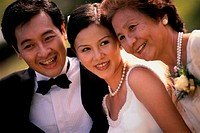 Close-up of a newlywed couple smiling with a mature woman