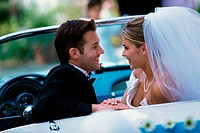 Side profile of a newlywed couple looking at each other in a convertible car