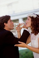 Side profile of a newlywed couple drinking champagne