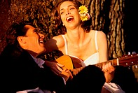 Bride and groom sitting together playing a guitar