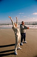 Side profile of a senior couple exercising on the beach