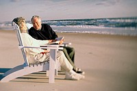 Senior couple sitting together on the beach