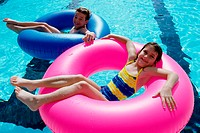High angle view of a boy and a girl lying on inflatable rings in a swimming pool (thumbnail)