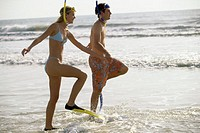 Side profile of a teenage couple walking on the beach wearing snorkels and flippers