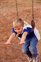 High angle view of a boy hanging on a swing
