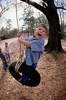 Boy swinging on a tire swing