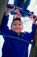 Portrait of a boy and a girl climbing on monkey bars