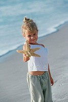 Portrait of a girl holding a starfish on the beach