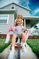 Portrait of two girls riding a tricycle