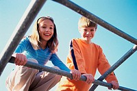 Portrait of a girl and a boy on monkey bars