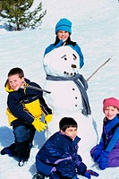 Portrait of a group of children making a snowman