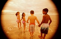Rear view of a group of children walking on the beach