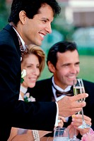 Newlywed young man toasting champagne with mid adult couple
