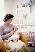 Mother sitting with her baby boy in nursery (thumbnail)