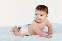 Baby boy crawling on a bed