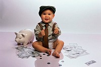 Portrait of a baby boy sitting on the floor with a piggy bank and money