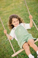 Front view of a girl sitting on a swing