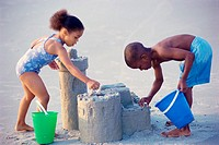 Side profile of a girl and a boy making sand castles on the beach