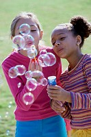 Close-up of two girls blowing bubbles with a bubble wand