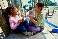 Side profile of two girls playing the clapping game