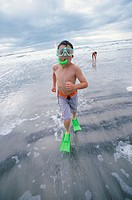 Portrait of a boy wearing a snorkel running on the beach