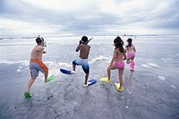 Rear view of two boys and two girls wearing snorkels and flippers walking on the beach