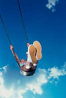 Low angle view of a girl swinging on a swing