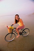 Portrait of a young woman cycling on the beach