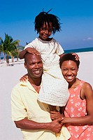 Portrait of parents carrying their daughter on their shoulders