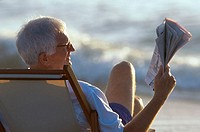Rear view of a senior man reading a newspaper on the beach