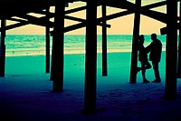 Silhouette of a young couple standing on the beach