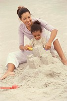 Mother and her daughter making a sand castle on the beach