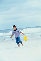 Boy running on the beach carrying a sand pail