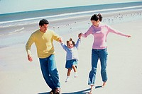Parents playing with their daughter on the beach