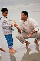 Father playing with his son on the beach