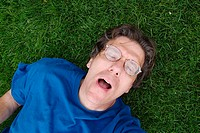 Middle age man, wearing glasses and eyes closed, lying on the grass in a park.