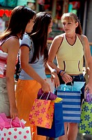 Side profile of three teenage girls standing with shopping bags