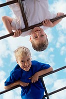 Portrait of two boys playing on monkey bars