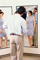 Mid adult couple standing in front of a mirror in the fitting room of a clothing store