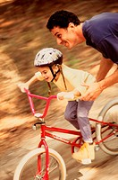 High angle view of a father teaching his daughter cycling