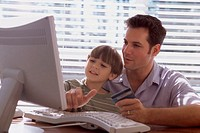 Father and his son sitting in front of a computer