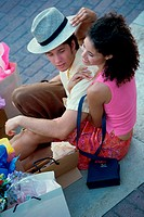 High angle view of a young couple sitting on the sidewalk with shopping bags