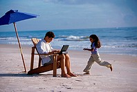 Father working on a laptop with his daughter running on the beach