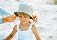 Father's hands putting hat on little boy, on beach