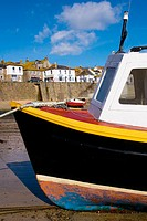 England, Cornwall, Mousehole harbour black white and yellow boat
