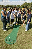 Hispanic students, golf putting game. North Shore Park, North Beach, Miami Beach, Florida. USA.