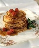 A Stack of Pancakes with Syrup and Raspberries