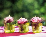 Three roses in decorated glasses